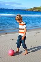 boy playing football on beach, Sutherland, Scotland