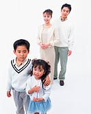 Two children posing in front of camera with their parents in the background