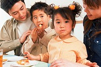 Family eating pizza at table