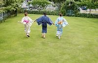 Three people in kimono holding hands