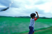 Indonesia, Bali, young boy flying kite in rice fields