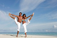 Couple doing exercises on the beach