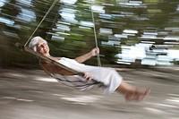 Maldives, Ari Atoll, senior woman swinging on hammock