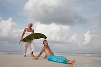 Maldives, Ari Atoll, senior couple with banana leaf on the beach