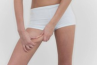 Woman pinching thigh, close_up