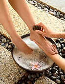Woman bathing feet in bowl with floating blossoms