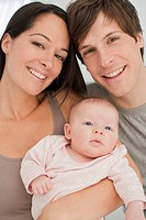 Close up of smiling parents holding baby