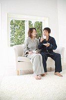 Mid adult couple sitting in sofa with cup in hand