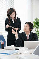 Young woman handing document to her boss