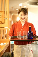 Waitress holding tray of glasses and bottle
