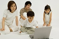 Family watching son use computer