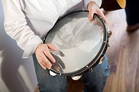 Young woman playing tambourine