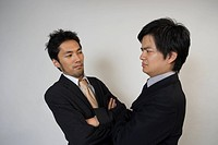 Two businessmen glaring each other