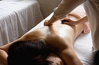 Young woman receiving stone massage