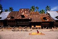 ASIA, INDONESIA, SUMATRA, NIAS ISLAND, BAWOMATALUO VILLAGE, WOMAN DRYING RICE IN STREET