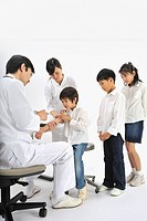 Male doctor and female nurse giving children injection