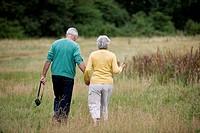 A senior couple walking through a field, carrying a camera