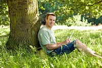 A young man leaning against a tree, using a laptop