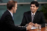 Caucasian man talking to Indian man at table