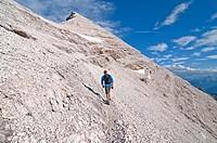 Man climbing the Giovanni Lipella via ferrata on Tofana De Rozes in the Dolomite Mountains near the city of Cortina in northern Italy