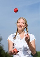 blond woman holding basket with apples,