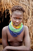 Nyangatom Bumi girl with piles of beads in front of her hut, Omo river Valley, Ethiopia