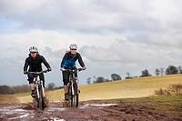 Couple riding bike through muddy puddles