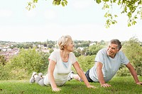 Mature couple doing push ups in park