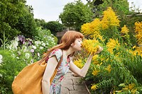 Woman smelling flowers in park