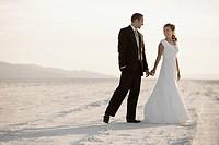 Bride and groom holding hands in desert