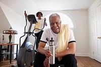 Black woman using elliptical machine, husband drinking water