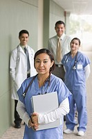 Hispanic doctor, surgeons and administrator in hospital corridor
