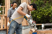 Asian construction worker using saw to cut lumber