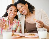 Mother and daughter eating cookies and milk together