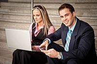 Man and woman working with laptop and phone on stairs