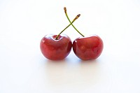 Two cherries on white background