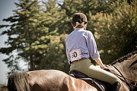 Young woman, her number pinned to her jacket, at a horse show.