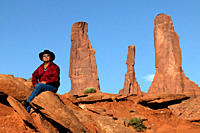Larry Holiday, Navajo guide sitting with the Three Sisters formation in Monument Valley Navajo Park, Utah, Arizona.
