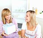 Beautiful woman receiving a present during a birthday party with her friend at home
