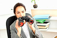 Serious hispanic businesswoman looking through binoculars sitting at her desk in her office