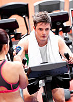 Female coach using a chronometer while man is doing physical exercises in a fitness centre