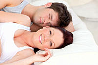 Lovely young couple resting in bed together in the bedroom