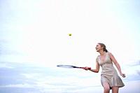 female tennis player balancing ball on racquet