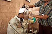 A man addicted to heroine, being stoned by a passerby, gets a dressing for his wounds, at Mary Adelaide, a church based NGO that operates from Karachi...