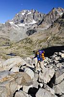 Man hiking at Colle dei Becchi, Gran Paradiso in background, Vallone dei Gias della Losa, Alta Via del Canavese, Gran Paradiso National Park, Piedmont...