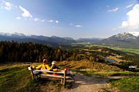 Couple hiking, enjoying the view from Kranzberg, View towards the Karwendel, Mittenwald, Upper Bavaria, Bavaria, Germany, Europe