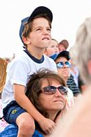 Young boy on mom´s shoulders watches the skys during air show at NAS Jacksonville, Florida