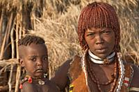 Young Hamar woman with necklaces made of Cowry shells and with red clay in her hair holding her baby in the arms, Omo river valley, Southern Ethiopia