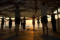 Group practicing Yoga at sunset on the beach, Goa, India