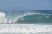 Surfers riding famous barrel waves Oahu, Hawaii